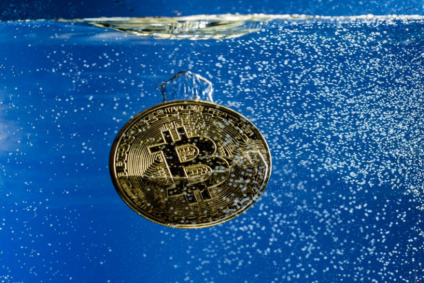Bitcoin sinking through water as illustration of falling price