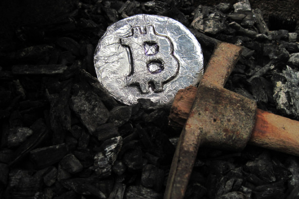 Bitcoin mining. A mine with real hardware. Symbols of block chain technology for crypto currency ? metal coin, coal, pickaxe