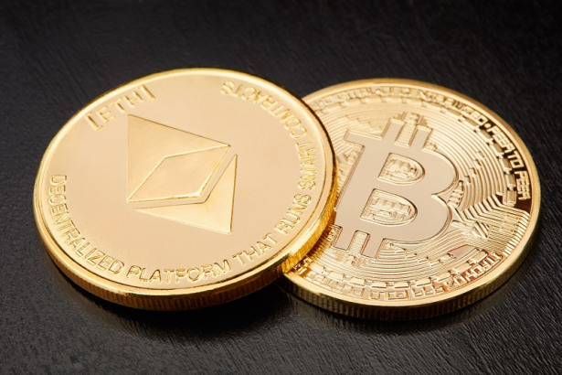 Ethereum and Bitcoin, two golden cryptocurrency coins on black background