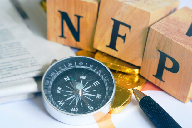 "Text ""NFP"" on wood cube with gold bar and compass and newspaper on the table, economic data concept"