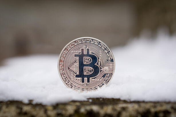 A silver Bitcoin placed in snow on concrete. Isolated scene of cryptocurrency in snow