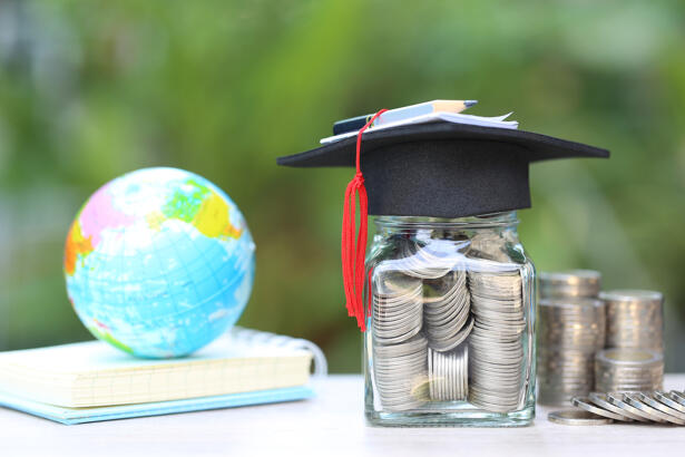 Graduation hat on the glass bottle and books on natural green background, Saving money
