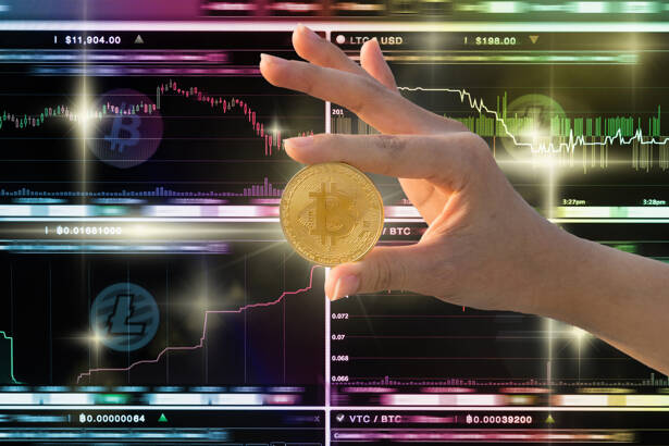 Closeup hand holding bitcoin over the Cryptocurrency trading scr