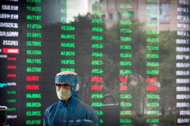 A worker wearing a protective suit stands in front of an electronic display board in the lobby of the Shanghai Stock Exchange building in Shanghai, Monday, Feb. 3, 2020. The Shanghai Composite index tumbled 8.7% Monday then rebounded slightly as Chinese regulators moved to stabilize markets reopening from a prolonged national holiday despite a rising death toll from a new virus that has spread to more than 20 countries. (AP Photo)