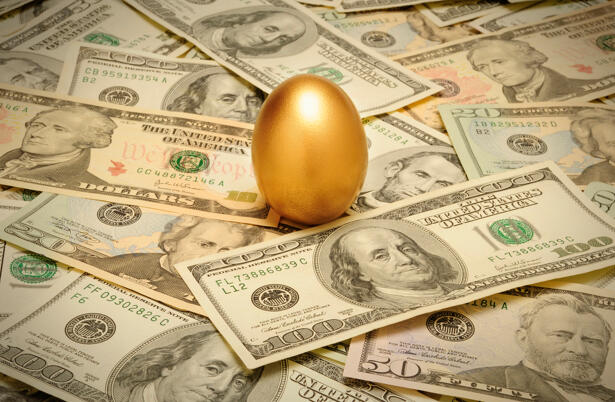 Gold nest egg on a layer of cash of various American banknote de