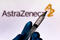 October 4, 2020, Brazil. In this photo illustration the medical syringe is seen with AstraZeneca company logo displayed on a screen in the background.