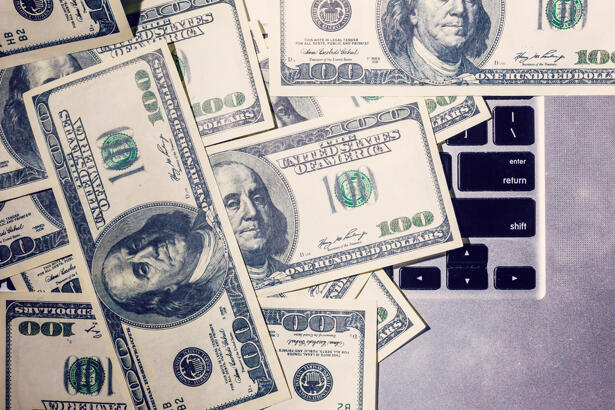 Closeup view of one hundred dollar banknotes lying on the laptop