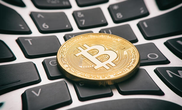 Golden bitcoin coin on keyboard