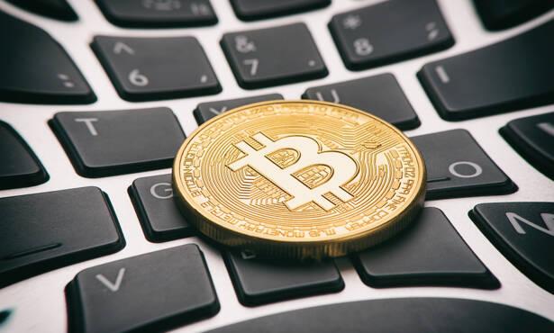 Golden bitcoin coin on keyboard