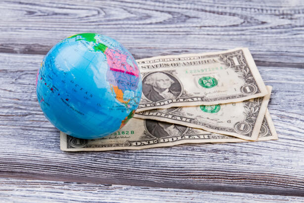 USA dollars banknotes and globe on wooden desk surface.