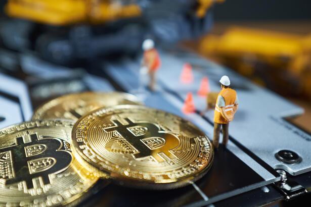 bitcoin mining concept; miniature Excavator and Bitcoin coins
