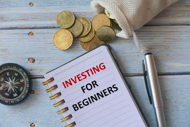 Top view of compass,gold coins,pen and notebook written with Investing for Beginners on wooden background.