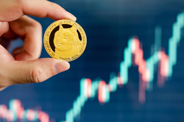 Hand holding gold Dogecoin with blurred candlestick chart
