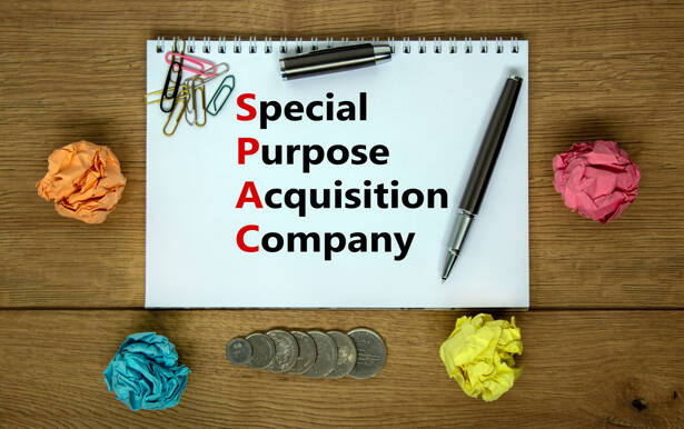 SPAC, special purpose acquisition company symbol. White note with words 'SPAC' on beautiful wooden background, copy space. Business and SPAC, special purpose acquisition company concept.