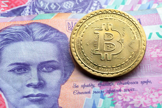 bitcoin symbol at ukrainian paper currency background. cryptocurrency technologies concept. virtual money with real life.