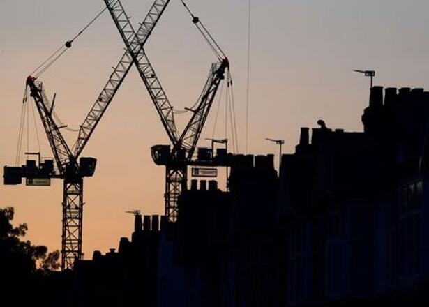 Construction cranes are seen on a residential building project behind homes in west London in Britain in this photograph taken on October 26
