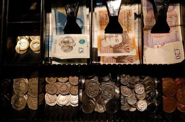 Pound Sterling notes and change are seen inside a cash