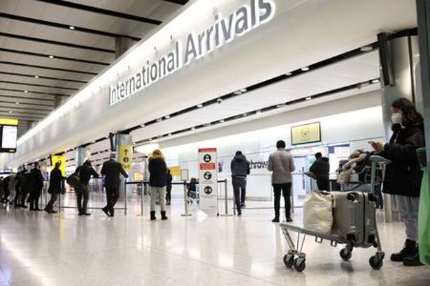 Travellers stand at Terminal 2 of Heathrow Airport,