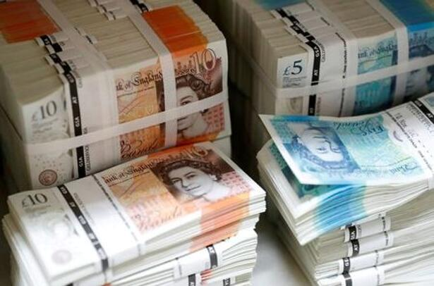Wads of British Pound Sterling banknotes are stacked