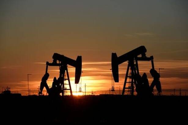 Pump jacks operate at sunset in an oil