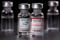 Picture illustration of vials with Pfizer-BioNTech and Moderna