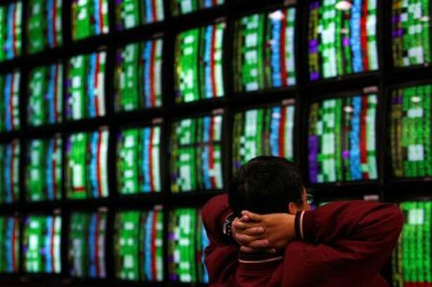 A man looks at stock market monitors in