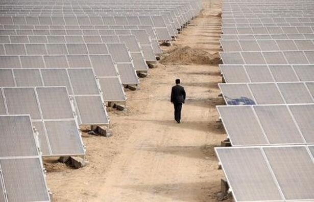 FILE PHOTO: A man walks through solar panels at a