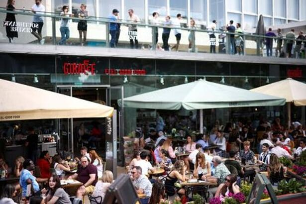 FILE PHOTO: People sit at an outdoor restaurant on the