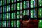 FILE PHOTO: A man looks at stock market monitors in
