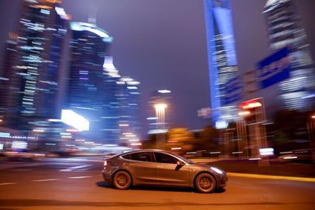 A Tesla electric car drives past a crossing