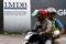 Motorcyclists pass a 1Malaysia Development Berhad (1MDB) billboard at the