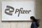 A person walks past a Pfizer logo in