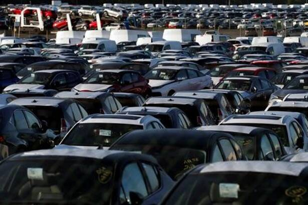 Stocks of new cars are parked in a lot, at