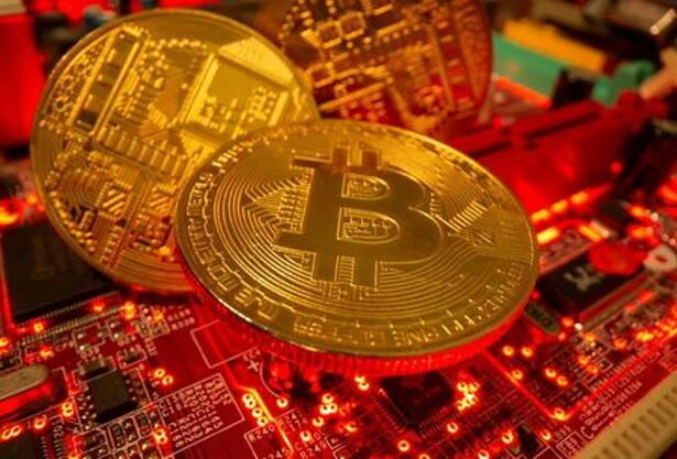 Representations of the virtual currency Bitcoin stand on a motherboard