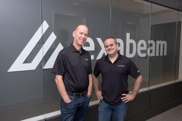 Exabeam CEO Michael DeCesare (L) and chairman and co-founder Nir Polak (R) pose in front of the Exabeam logo in Foster City, California in this undated handout photograph.