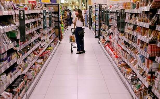 FILE PHOTO: A shopper wearing a protective mask pushes a