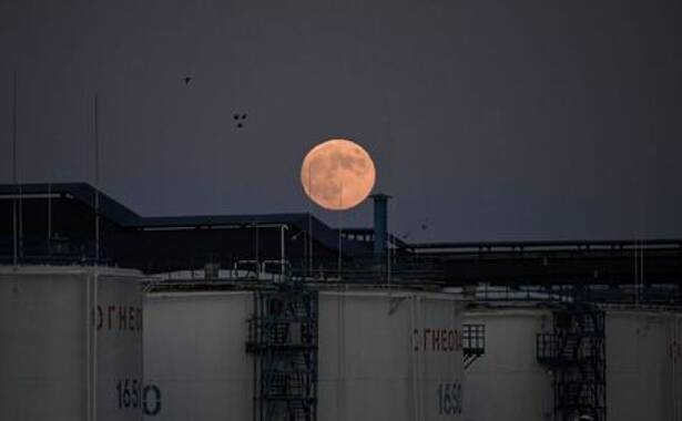 FILE PHOTO: The moon rises behind oil storage tanks in