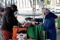 A lady pays for fruit and vegetables from a market