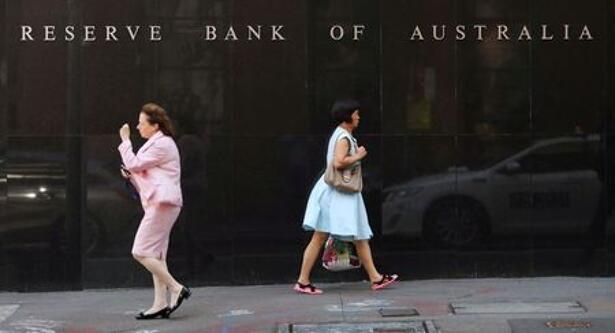 Two women walk next to the Reserve Bank