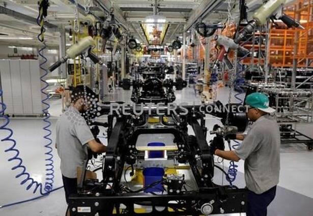 Homens trabalham em linha de montagem de caminhões da Mercedes