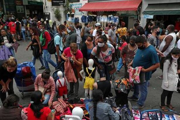 Pessoas observam roupas à venda em rua comercial popular em