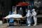 Profissionais de um necrotério colocam corpo de pessoa que morreu