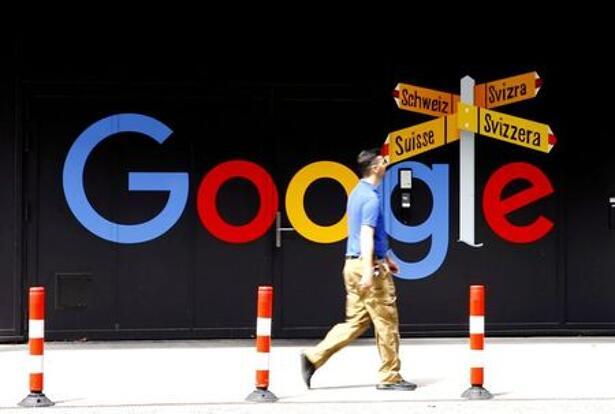 FILE PHOTO: A man walks past a logo of Alphabet