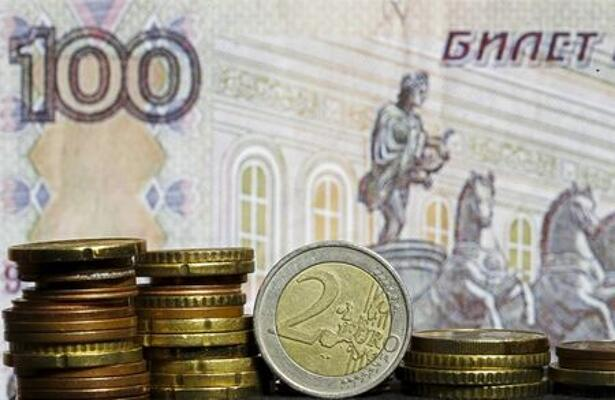 Euro coins are seen in front of a banknote of