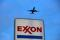 An airplane comes in for a landing above an Exxon
