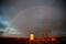 A rainbow is seen over a pumpjack during sunset outside