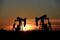 FILE PHOTO: Pump jacks operate at sunset in an oil