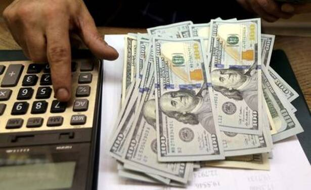 FILE PHOTO: An employee counts U.S. dollar bills at a