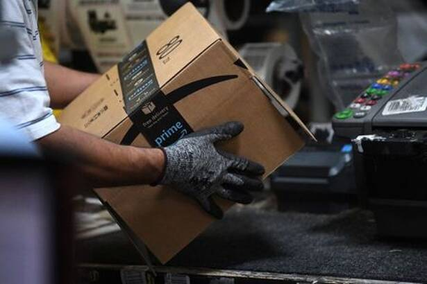 Worker assembles a box for delivery at the Amazon fulfilment