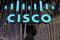 A man passes under a Cisco logo at the Mobile